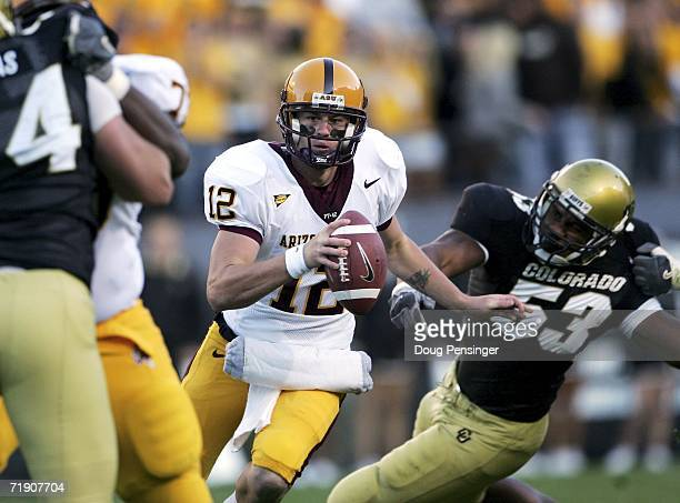 Quarterback Rudy Carpenter of the Arizona State Sun Devils looks for a receiver as Abraham Wright of the University of Colorado Buffaloes pressures...