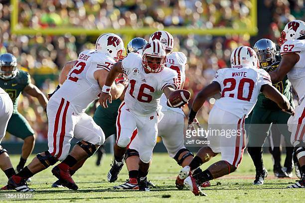 Quarterback Russell Wilson hands the ball off to running back James White of the Wisconsin Badgers while taking on the Oregon Ducks at the 98th Rose...