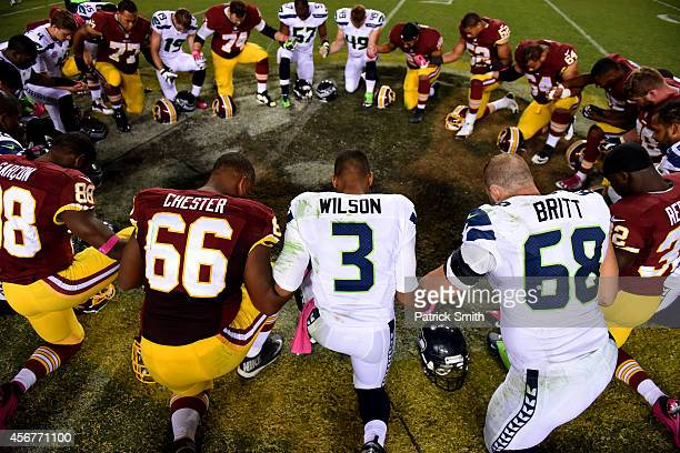 Quarterback Russell Wilson of the Seattle Seahawks and players from the Seattle Seahawks and the Washington Redskins pray following an NFL game at...