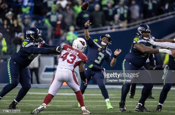 Quarterback Russell Wilson of the Seattle Seahawks attempts a pass as he is pressured by linebacker Haason Reddick of the Arizona Cardinals during...