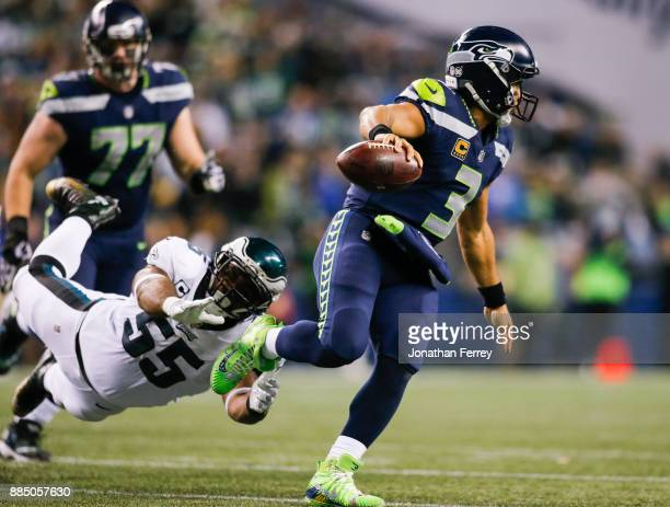 Quarterback Russell Wilson of the Seattle Seahawks avoids a tackle from defensive end Brandon Graham of the Philadelphia Eagles in the third quarter...