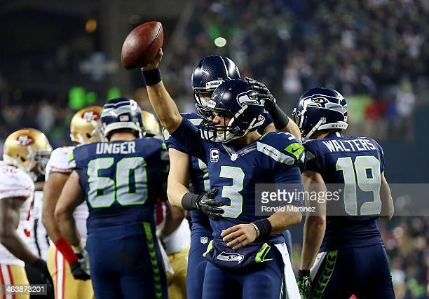 Quarterback Russell Wilson of the Seattle Seahawks celebrates as the Seahawks defeat the San Francisco 49ers 2317 during the 2014 NFC Championship at...