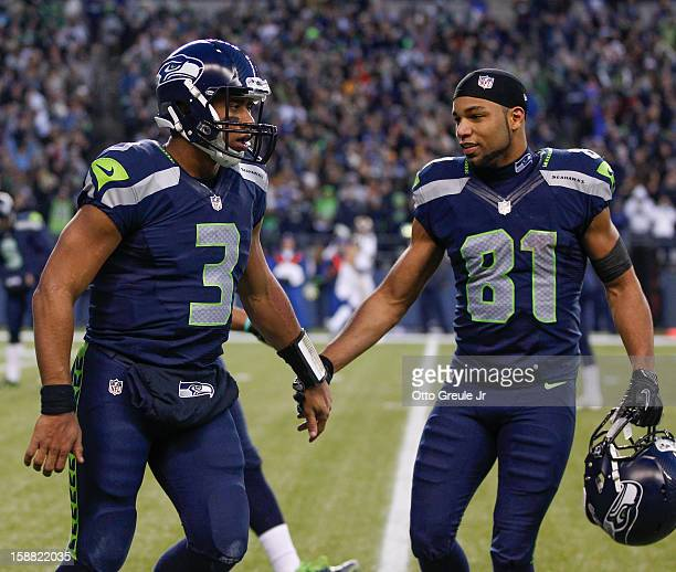 Quarterback Russell Wilson of the Seattle Seahawks celebrates with wide receiver Golden Tate after scoring a touchdown against the St Louis Rams at...