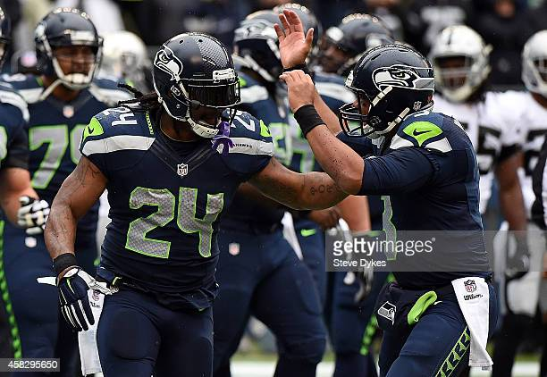 Quarterback Russell Wilson of the Seattle Seahawks celebrates with running back Marshawn Lynch of the Seattle Seahawks after Lynch scored a touchdown...