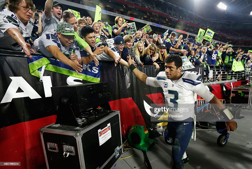 Quarterback Russell Wilson #3 of the Seattle Seahawks celebrates with fans after defeating the Arizona Cardinals 35-6 in the NFL game at the University of Phoenix Stadium on December 21, 2014 in Glendale, Arizona.