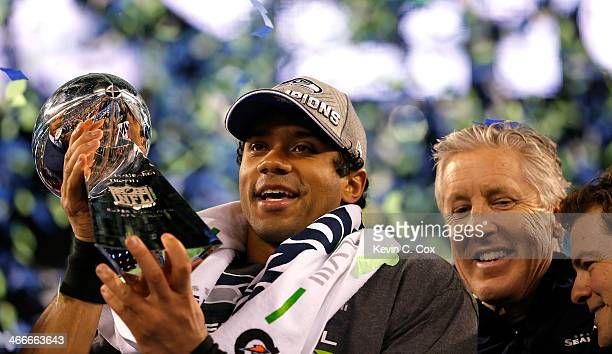Quarterback Russell Wilson of the Seattle Seahawks celebrates with the Vince Lombardi Trophy alongside head coach Pete Carroll after their 438...