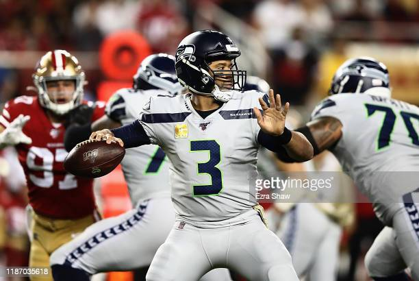 Quarterback Russell Wilson of the Seattle Seahawks delivers a pass over the defense of the San Francisco 49ers the game at Levi's Stadium on November...
