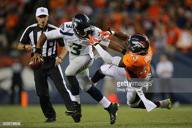 Quarterback Russell Wilson of the Seattle Seahawks draws a face mask penalty as he stiffarms strong safety TJ Ward of the Denver Broncos during...