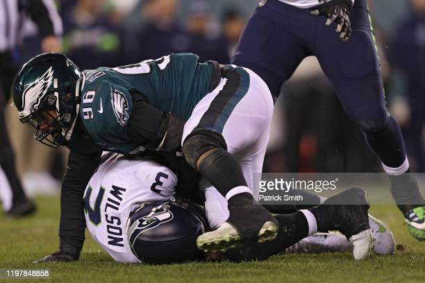 Quarterback Russell Wilson of the Seattle Seahawks draws a late hit penalty by defensive end Derek Barnett of the Philadelphia Eagles during the...