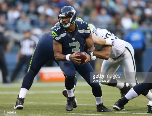 Quarterback Russell Wilson of the Seattle Seahawks drops back against the Oakland Raiders at CenturyLink Field on August 30 2012 in Seattle Washington
