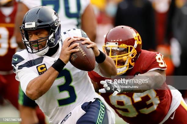 Quarterback Russell Wilson of the Seattle Seahawks eludes the tackle of defensive tackle Jonathan Allen of the Washington Football Team in the second...