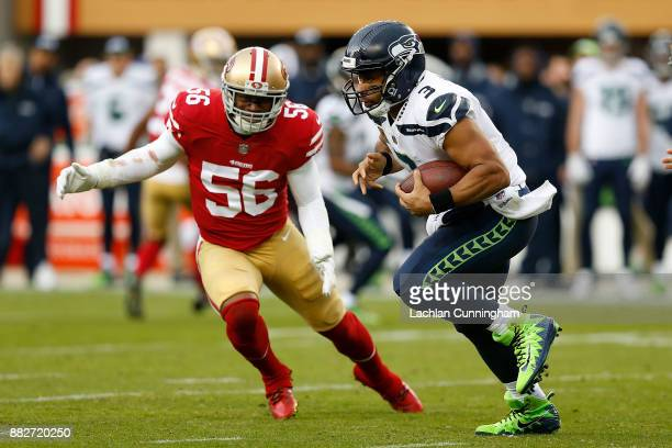 Quarterback Russell Wilson of the Seattle Seahawks evades Reuben Foster of the San Francisco 49ers at Levi's Stadium on November 26 2017 in Santa...