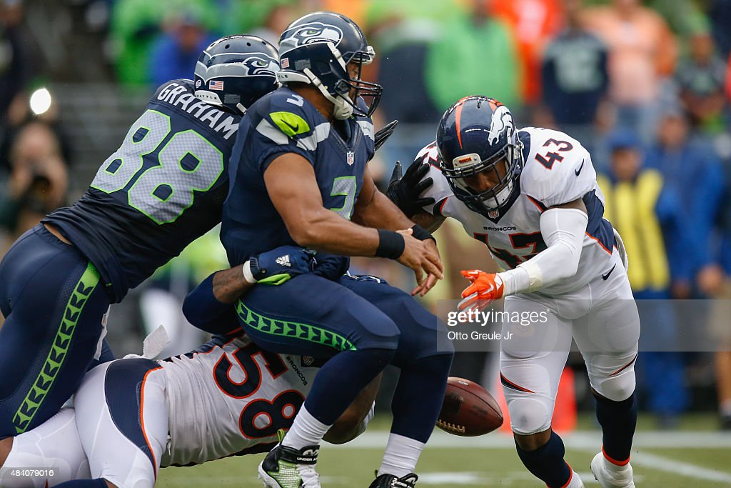 Quarterback Russell Wilson #3 of the Seattle Seahawks fumbles as he is tackled by linebacker Von Miller #58 of the Denver Broncos at CenturyLink Field on August 14, 2015 in Seattle, Washington. The Broncos defeated the Seahawks 22-20.