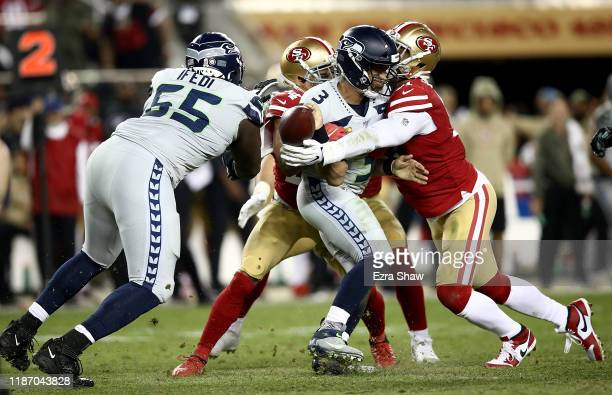 Quarterback Russell Wilson of the Seattle Seahawks fumbles the ball caused by the defense of defensive end Arik Armstead of the San Francisco 49ers...