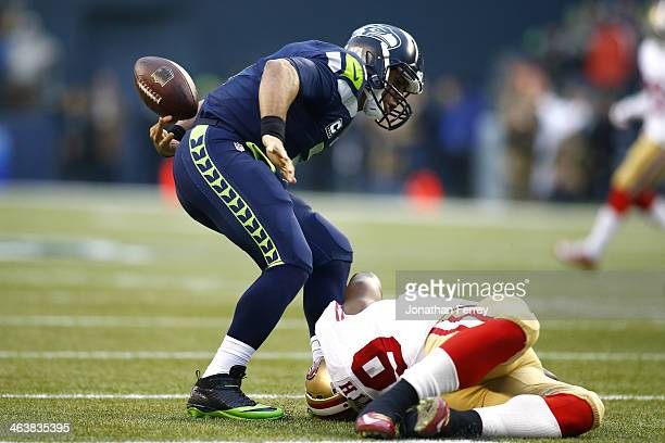 Quarterback Russell Wilson of the Seattle Seahawks fumbles the ball in the first quarter after being tackled by outside linebacker Aldon Smith of the...