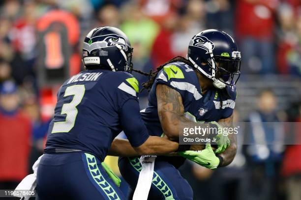 Quarterback Russell Wilson of the Seattle Seahawks hands off the ball to teammate running back Marshawn Lynch during the first half of the game...