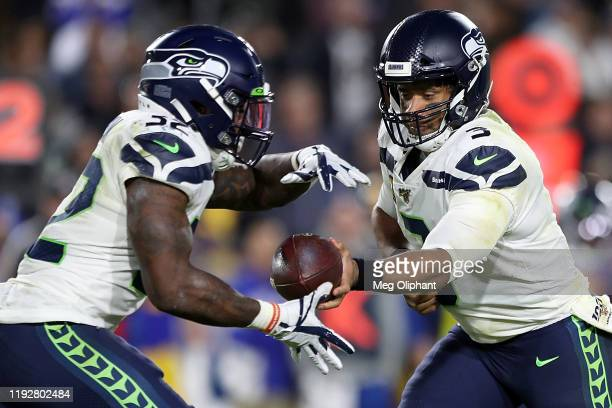 Quarterback Russell Wilson of the Seattle Seahawks hands off to running back Chris Carson during the game against the Los Angeles Rams at Los Angeles...