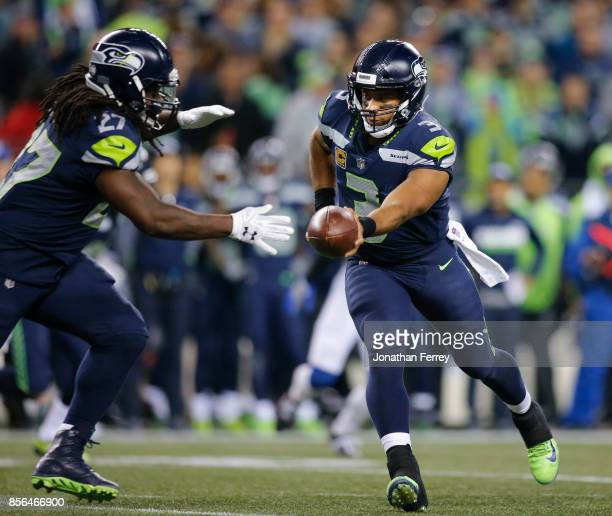 Quarterback Russell Wilson of the Seattle Seahawks hands off to running back Eddie Lacy in the third quarter of the game at CenturyLink Field on...