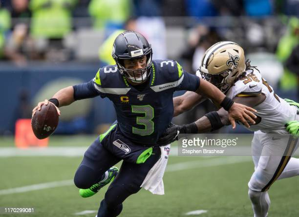 Quarterback Russell Wilson of the Seattle Seahawks is chased out of the pocket by linebacker Demario Davis of the New Orleans Saints during the...