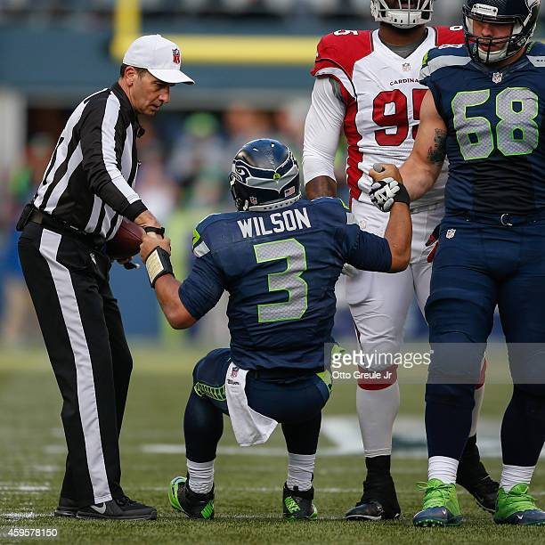 Quarterback Russell Wilson of the Seattle Seahawks is helped up by tackle Justin Britt and referee Gene Steratore against the Arizona Cardinals at...