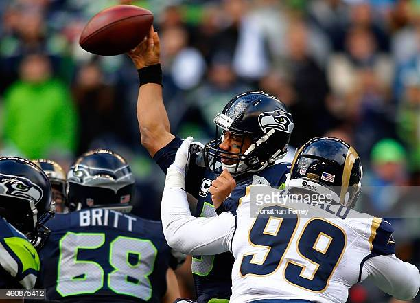Quarterback Russell Wilson of the Seattle Seahawks is hit by defensive tackle Aaron Donald of the St Louis Rams as he passes the ball during the...