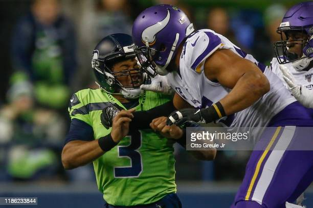 Quarterback Russell Wilson of the Seattle Seahawks is pressured by linebacker Anthony Barr of the Minnesota Vikings after throwing a pass in the...