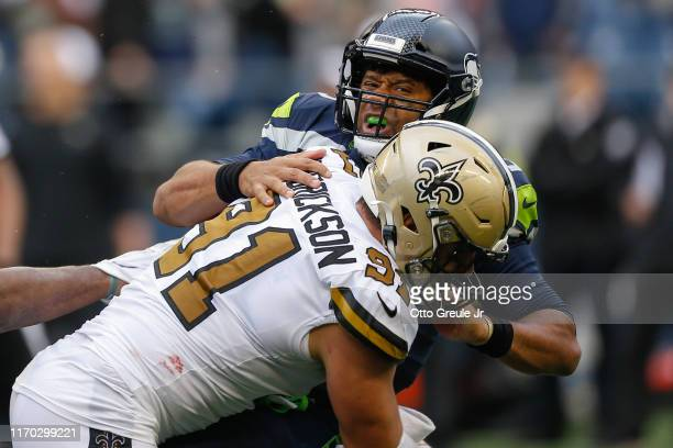 Quarterback Russell Wilson of the Seattle Seahawks is sacked by defensive end Trey Hendrickson of the New Orleans Saints at CenturyLink Field on...