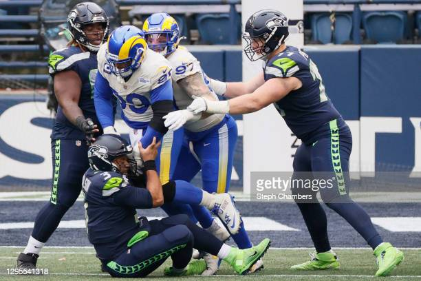 Quarterback Russell Wilson of the Seattle Seahawks is sacked by defensive end Aaron Donald of the Los Angeles Rams during the NFC Wild Card Playoff...