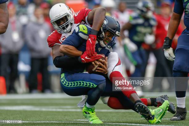 Quarterback Russell Wilson of the Seattle Seahawks is sacked by linebacker Chandler Jones of the Arizona Cardinals in the second quarter at...