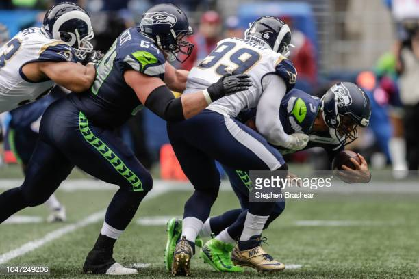 Quarterback Russell Wilson of the Seattle Seahawks is sacked by Defensive Tackle Aaron Donald of the Los Angeles Rams in the first half at...