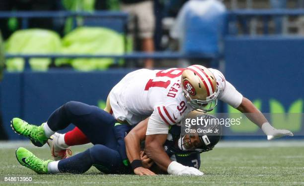 Quarterback Russell Wilson of the Seattle Seahawks is sacked by defensive lineman Arik Armstead of the San Francisco 49ers for a loss of 8 yards...