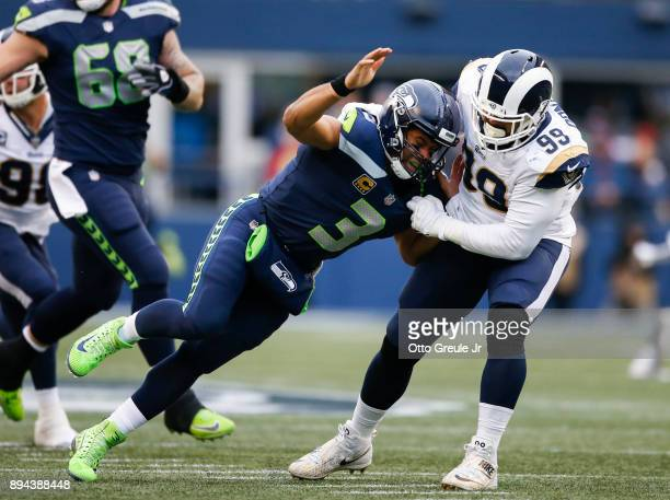 Quarterback Russell Wilson of the Seattle Seahawks is sacked by defensive tackle Aaron Donald of the Los Angeles Rams in the second quarter at...