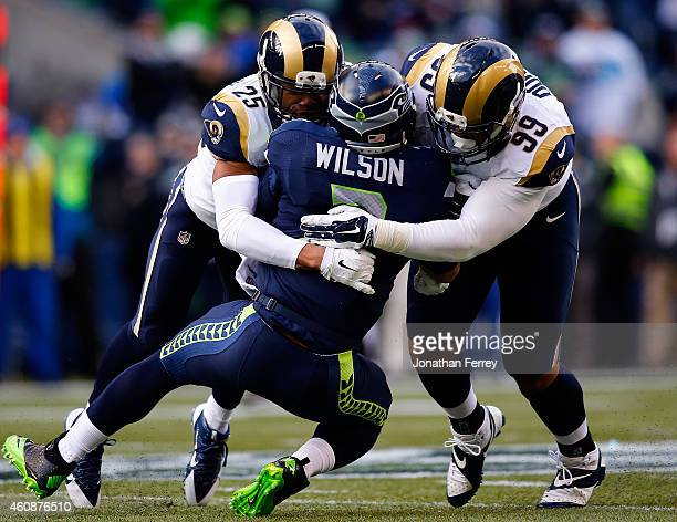 Quarterback Russell Wilson of the Seattle Seahawks is tackled by strong safety TJ McDonald of the St Louis Rams and defensive tackle Aaron Donald of...