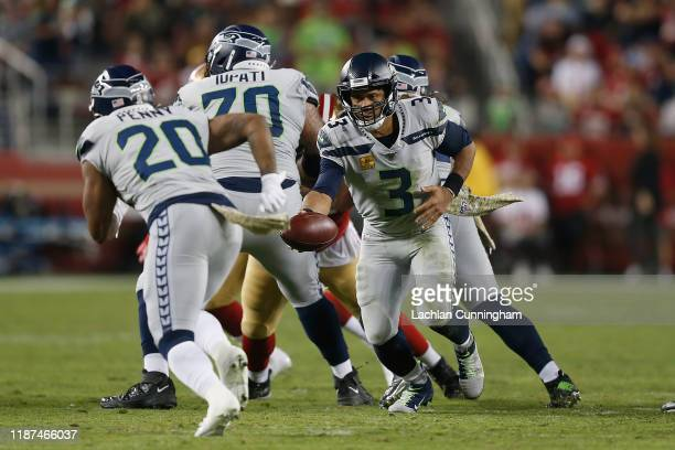 Quarterback Russell Wilson of the Seattle Seahawks looks to hand the ball off to Rashaad Penny in the second quarter against the San Francisco 49ers...