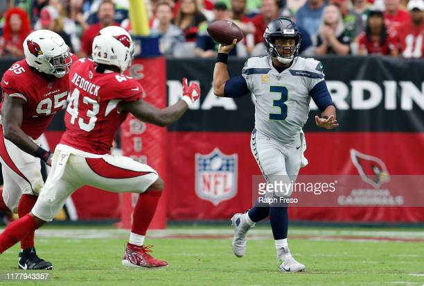 Quarterback Russell Wilson of the Seattle Seahawks looks to pass as he is pressured by linebacker Haason Reddick and defensive lineman Rodney Gunter...