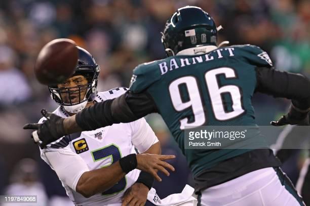 Quarterback Russell Wilson of the Seattle Seahawks passes the ball past defensive end Derek Barnett of the Philadelphia Eagles during their NFC Wild...