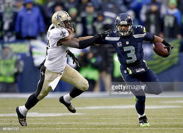 Quarterback Russell Wilson of the Seattle Seahawks pushes back strong safety Roman Harper of the New Orleans Saints in the fourth quarter while...