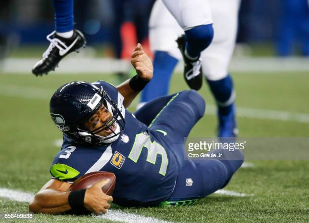 Quarterback Russell Wilson of the Seattle Seahawks reaches into the end zone to score a 23 yard touchdown against the Indianapolis Colts in the third...