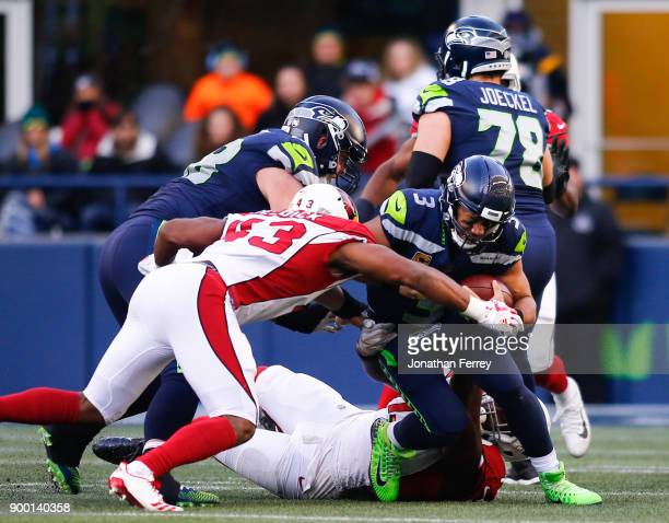 Quarterback Russell Wilson of the Seattle Seahawks runs into a tackle by inside linebacker Haason Reddick of the Arizona Cardinals in the second half...