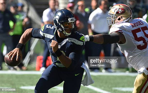 Quarterback Russell Wilson of the Seattle Seahawks runs out of the grasp of outside linebacker Ahmad Brooks of the San Francisco 49ers the first...