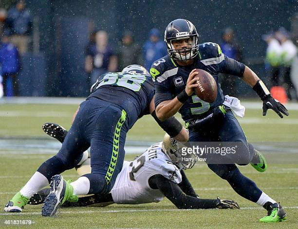 Quarterback Russell Wilson of the Seattle Seahawks runs the ball against the New Orleans Saints in the second quarter during the NFC Divisional...