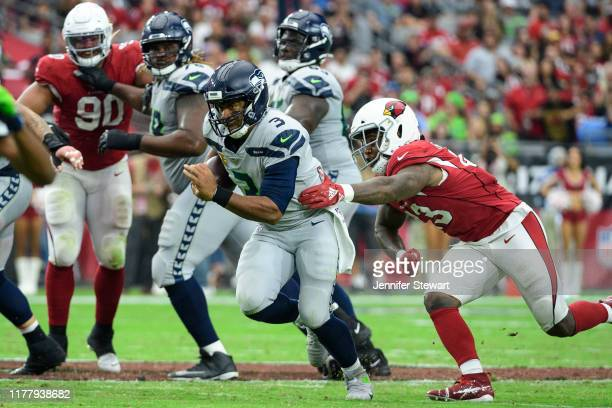 Quarterback Russell Wilson of the Seattle Seahawks runs with the ball against outside linebacker Haason Reddick of the Arizona Cardinals in the...