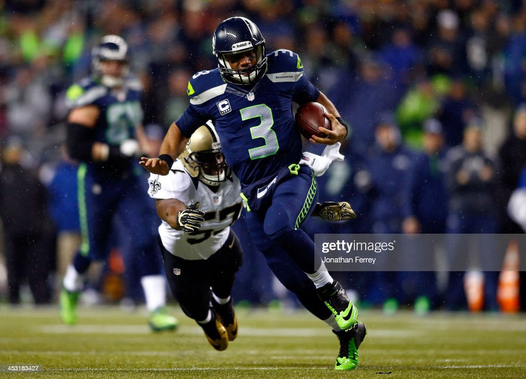 Quarterback Russell Wilson #3 of the Seattle Seahawks runs with the ball as outside linebacker David Hawthorne #57 of the New Orleans Saints defends during a game at CenturyLink Field on December 2, 2013 in Seattle, Washington.