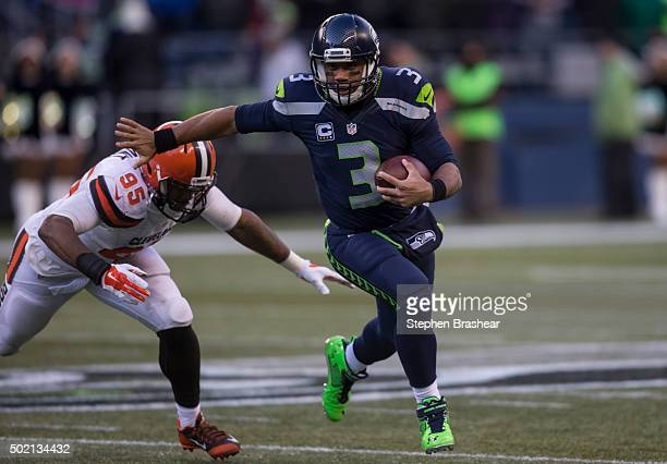 Quarterback Russell Wilson of the Seattle Seahawks runs with the ball as defensive lineman Armonty Bryant of the Cleveland Browns tries to make the...