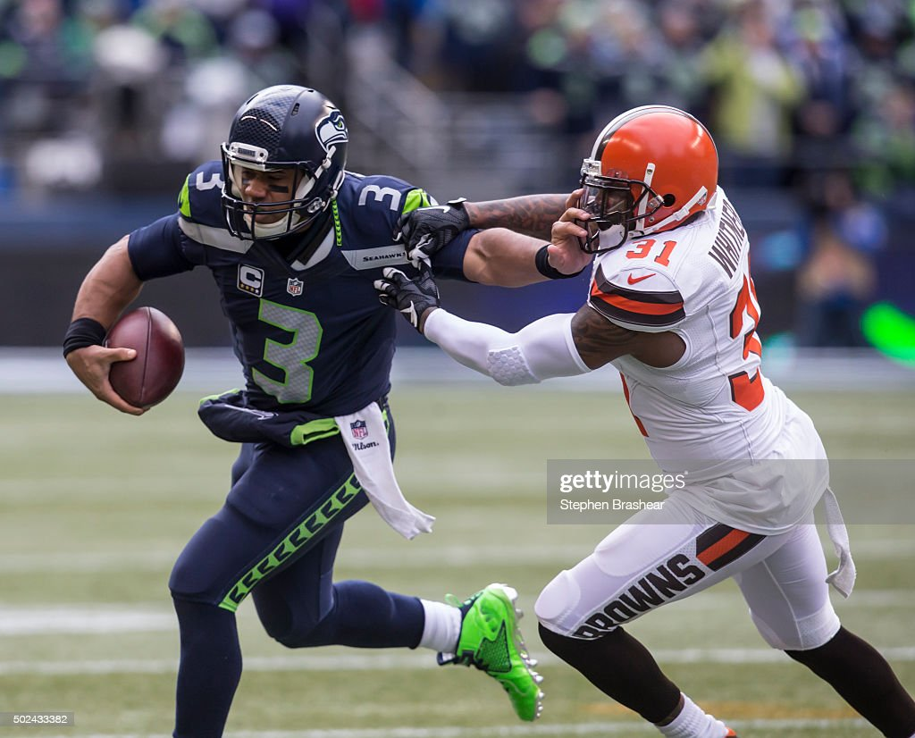 Quarterback Russell Wilson #3 of the Seattle Seahawks runs with the ball as defensive back Donte Whitner #31 of the Cleveland Browns tries to make a tackle during the first half a football game at CenturyLink Field on December 20, 2015 in Seattle, Washington. The Seahawks won the game 30-13.