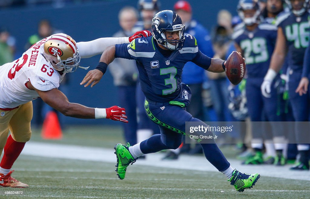 Quarterback Russell Wilson #3 of the Seattle Seahawks rushes against Tony Jerod-Eddie #63 of the San Francisco 49ers at CenturyLink Field on November 22, 2015 in Seattle, Washington.