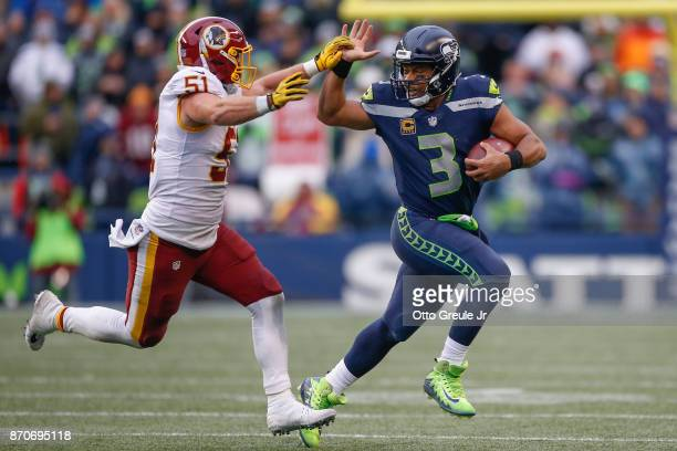 Quarterback Russell Wilson of the Seattle Seahawks rushes against linebacker Will Compton of the Washington Redskins at CenturyLink Field on November...