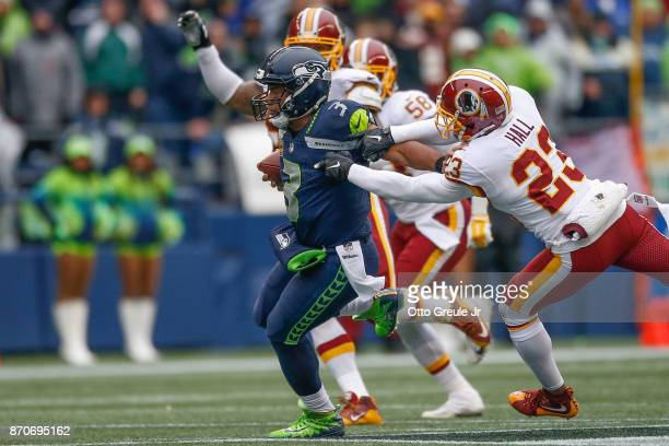 Quarterback Russell Wilson of the Seattle Seahawks rushes against safety DeAngelo Hall of the Washington Redskins at CenturyLink Field on November 5...