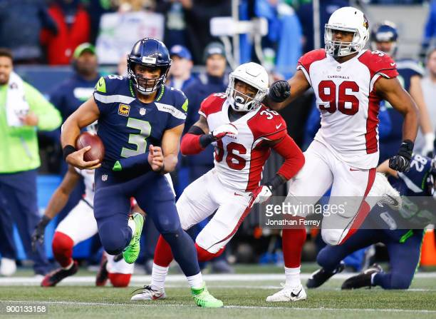 Quarterback Russell Wilson of the Seattle Seahawks rushes for 31 yards in the fourth quarter against the Arizona Cardinals including Budda Baker and...