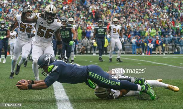 Quarterback Russell Wilson of the Seattle Seahawks scores a touchdown against cornerback Marshon Lattimore of the New Orleans Saints at CenturyLink...
